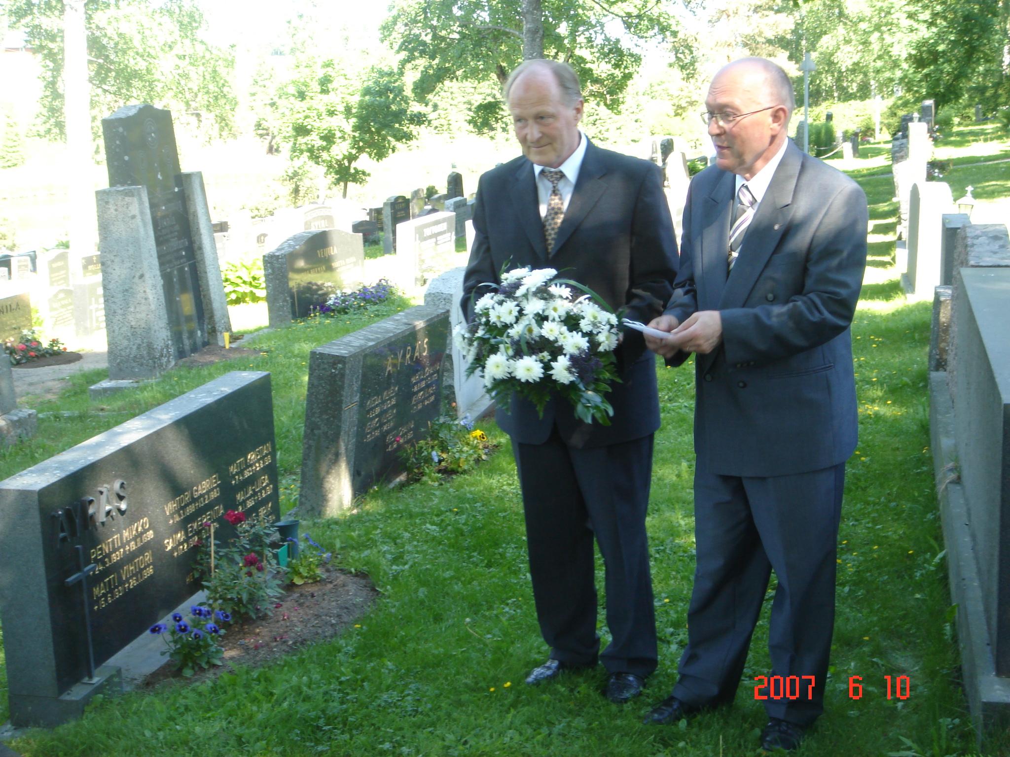 Reijo Vuola (K) vas. ja Hannu Vuola (K) laskivat kukat Kaarle ja Alma Vuolan haudalle